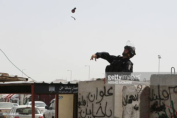 An Israeli border guard throws a tear gas grenade towards Palestinian protesters during clashes at the Qalandia checkpoint between the cities of...
