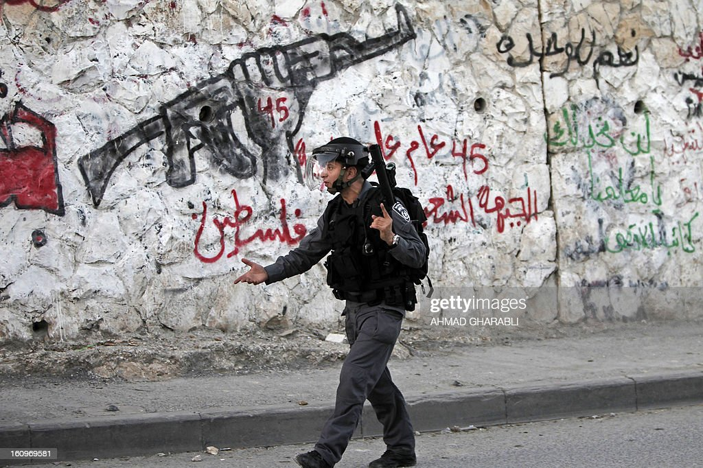 An Israeli border guard walks in front of a wall covered in graffiti during clashes with Palestinian protestors in the Arab Jerusalem neighbourhood of Issawiya on February 8, 2013, during a demonstration in solidarity with Palestinian prisoner Samer Issawi, who is held in an Israeli jail and has been on hunger strike for more than 200 days. Police and border guard forces dispersed the protestors using shock grenades after a number of Palestinian youths hurled rocks at them.