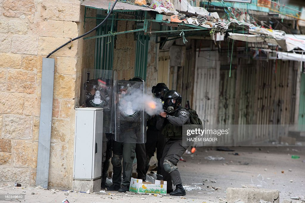 An Israeli border guard wearing a gas mask fires a smoke grenade at Palestinian protestors who are demanding the right of access to the street that can only be used by Israeli settlers, during clashes in al-Shuhada street in the West Bank town of Hebron on February 22, 2013.