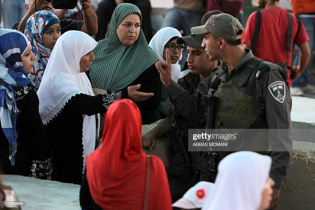 An Israeli border police gestures to Palestinian Muslim worshipers waiting to cross the Qalandia checkpoint between Ramallah and Jerusalem on their way to attend the first Friday prayers of Ramadan in the Al-Aqsa mosque compound on July 12, 2013.