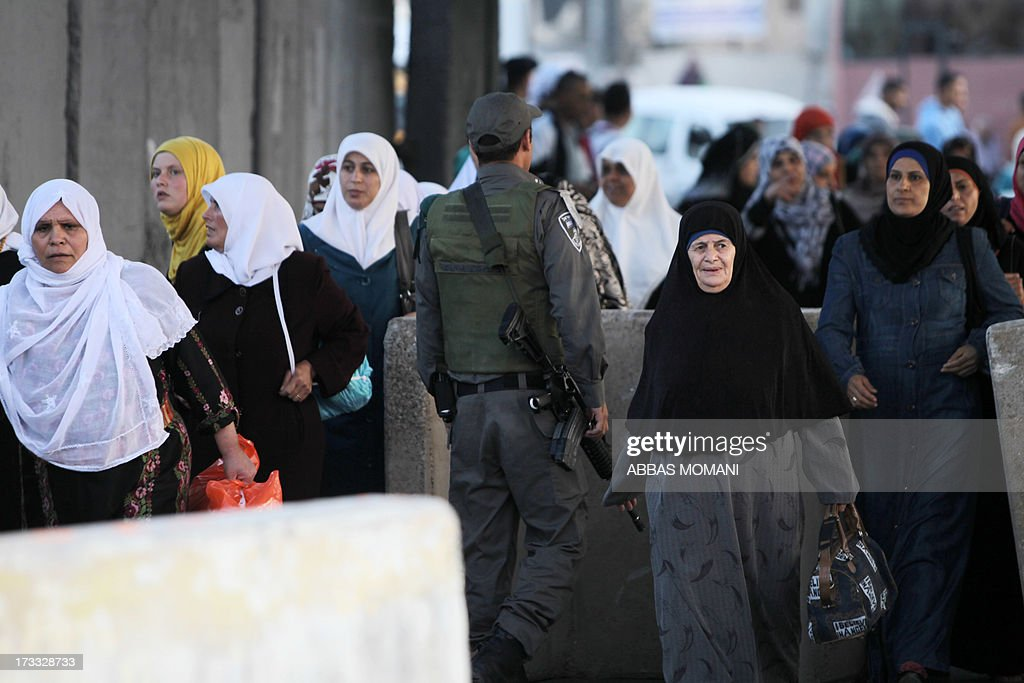 An Israeli border police stands guard among Palestinian Muslim worshipers crossing the Qalandia checkpoint between Ramallah and Jerusalem on their way to attend the first Friday prayers of Ramadan in the Al-Aqsa mosque compound on July 12, 2013.