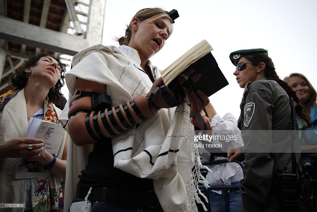 An Israeli Border Police woman stands guard near members of the liberal Jewish religious group Women of the Wall wearing phylacteries and the 'Tallit' shawl, traditional Jewish prayer apparel for men, as they pray at the Western Wall in Jerusalem's Old City on June 9, 2013 marking the first day of the Jewish month of Tamuz.