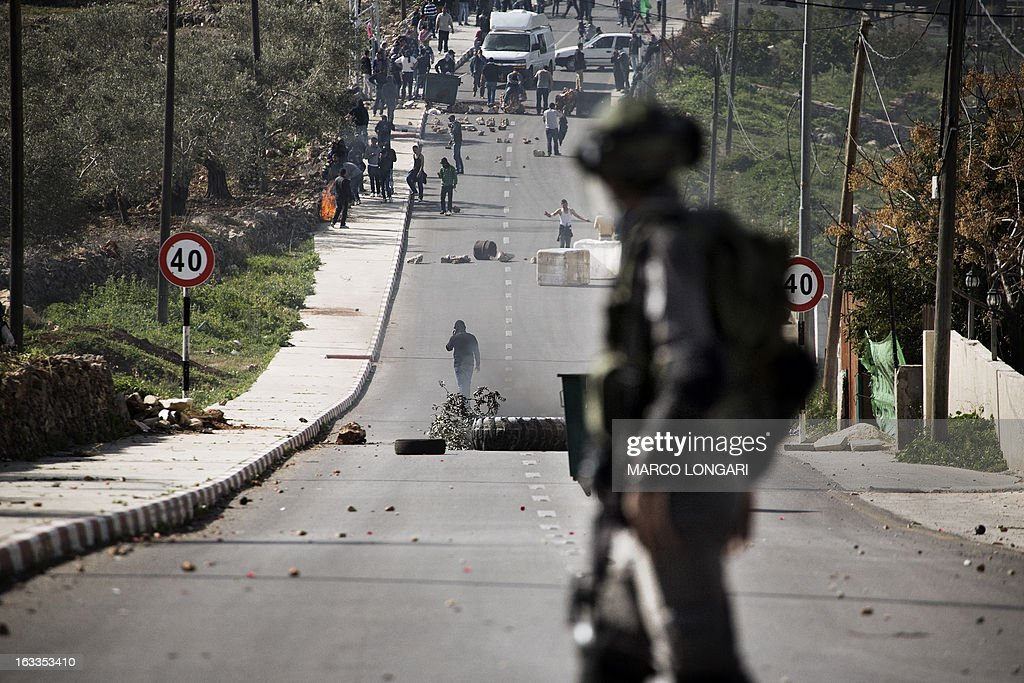 An Israeli border policeman confronts a group of Palestinian stone throwers during clashes following the funeral of Mohammad Asfour in the West Bank village of Abud on March 8, 2013. Asfour died of his wounds on March 7, after he was hit by a rubber-coated steel bullet during a demonstration over the death of a Palestinian prisoner in Israeli custody in February.