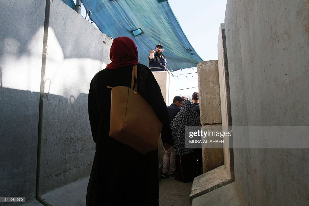 An Israeli border policeman gestures towards a Palestinian woman as Palestinians cross an Israeli checkpoint between the West Bank town of Bethlehem and Jerusalem, as they head to Jerusalem's Al-Aqsa Mosque compound on the forth and last Friday of the Muslim holy month of Ramadan on July 1 , 2016. Israeli authorities announced on June 28 they were closing Jerusalem's flashpoint Al-Aqsa mosque compound to non-Muslim visitors until the end of the Muslim holy month of Ramadan after a series of clashes between worshippers and Israeli police. Clashes have been taking place every morning since the beginning of the week over Jewish visits to the site, with youths throwing stones and security forces firing tear gas and sponge-tipped bullets. / AFP / MUSA