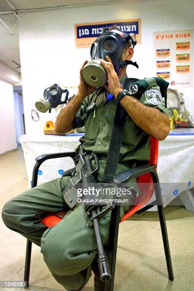An Israeli border policeman measures himself a gas mask at a distribution center in a shopping mall August 21 2002 in Jerusalem Israel Citizens and...