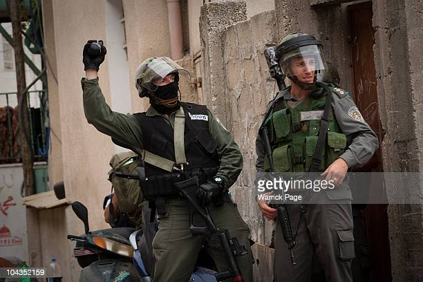 An Israeli border policeman prepares to throw a sound grenade during clashes in the Palestinian neighbourhood of Silwan after the funeral procession...