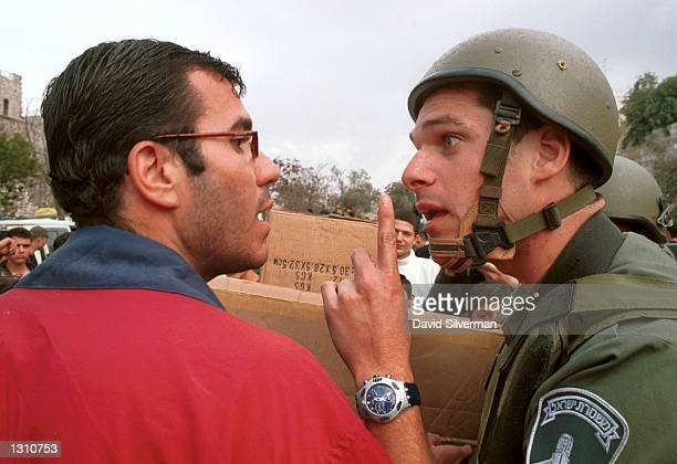 An Israeli Border Policeman right warns off a Palestinian man after the he refused to move away from the the Damascus Gate area December 8 2000...