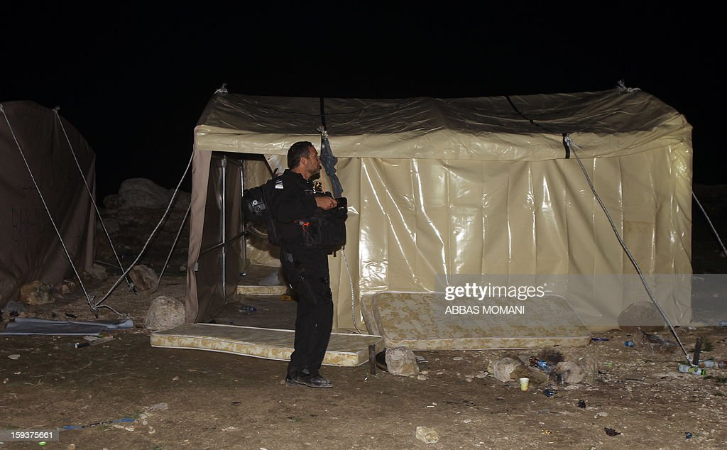 An Israeli border policeman searches an outpost of tents as they prepare to evict Palestinian protesters from the scene in the controversial West Bank area known as E1 between Israeli annexed east Jerusalem and the settlement of Maaleh Adumim early on January 13, 2013. Israeli police early on January 13 evicted Palestinian protesters from a hilltop camp they set up in a West Bank area slated for Jewish settlement, police and witnesses said. AFP PHOTO / ABBAS MOMANI