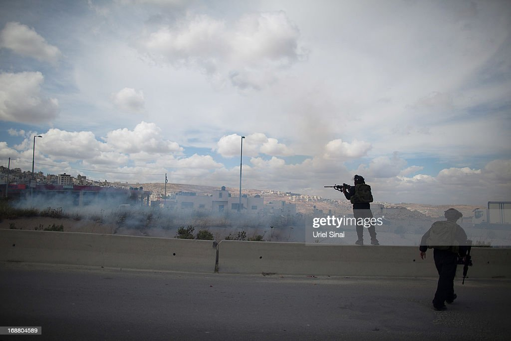An Israeli border policeman shoots rubber bullets during clashes with Palestinian protesters during Nakba day on May 15, 2013 near the Qalandia checkpoint at the outskirts of Ramallah, the West Bank. Palestinians mark Israel's establishment in 1948 with 'Nakba' or 'catastrophe' day on May 15, to remember the thousands of Palestinians who fled or were expelled during the creation of the Jewish state and the subsequent war.