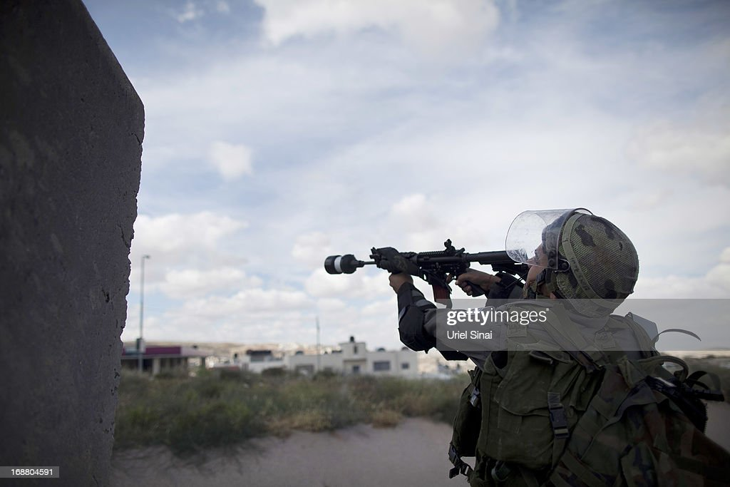 An Israeli border policeman shoots tear gas during clashes with Palestinian protesters during Nakba day on May 15, 2013 near the Qalandia checkpoint at the outskirts of Ramallah, the West Bank. Palestinians mark Israel's establishment in 1948 with 'Nakba' or 'catastrophe' day on May 15, to remember the thousands of Palestinians who fled or were expelled during the creation of the Jewish state and the subsequent war.