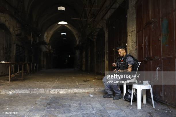 An Israeli border policeman sits as he guards a street in Jerusalem's Old City on July 16 after security forces reopened the ultrasensitive AlAqsa...