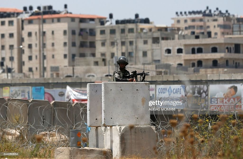 An Israeli border policeman stands guard during clashes with young Palestinians at the Qalandia checkpoint between Ramallah and Jerusalem on July 1, 2016, as Israeli authorities banned men under 45 from accessing the Al-Aqsa mosque compound for Friday prayers. The Palestinian health ministry said that a middle-aged man had died from tear gas fired by Israeli forces during a clash at the Qalandia crossing. Israeli police said in a statement that three members of the security forces were injured by stones but it reported no Palestinian casualties. / AFP / ABBAS