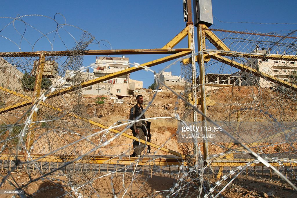 An Israeli border policeman stands guard near a gap in the barbed-wire gate part of the controversial Israeli separation fence between the West Bank town of Bethlehem and Jerusalem, after an attempt by Palestinian men to sneak in and reach the Al-Aqsa Mosque compound in Jerusalem through it, following an order by Israeli police two days earlier to prevent Palestinians from crossing to pray on the fourth and last Friday of the Muslim holy month of Ramadan due to a rise in violence at the site, on July 1, 2016. Israeli authorities announced on June 28 they were closing Jerusalem's flashpoint Al-Aqsa mosque compound to non-Muslim visitors until the end of the Muslim holy month of Ramadan after a series of clashes between worshippers and Israeli police. Clashes have been taking place every morning since the beginning of the week over Jewish visits to the site, with youths throwing stones and security forces firing tear gas and sponge-tipped bullets. / AFP / MUSA
