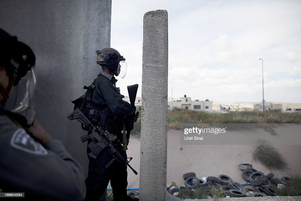 An Israeli border policeman takes cover during clashes with Palestinian protesters army during Nakba day on May 15, 2013 near the Qalandia checkpoint at the outskirts of Ramallah, the West Bank. Palestinians mark Israel's establishment in 1948 with 'Nakba' or 'catastrophe' day on May 15, to remember the thousands of Palestinians who fled or were expelled during the creation of the Jewish state and the subsequent war.