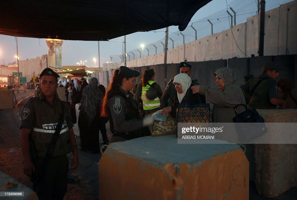 An Israeli border policewoman checks the belongings of Palestinian Muslim worshipers crossing the Qalandia checkpoint between Ramallah and Jerusalem on their way to attend the first Friday prayers of Ramadan in the Al-Aqsa mosque compound on July 12, 2013.
