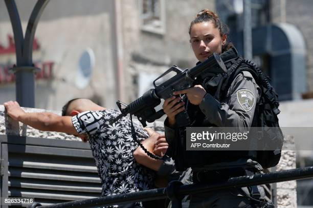 TOPSHOT An Israeli border policewoman holds her weapon while checking the ID of Palestinians on their way to Friday noon prayer at the AlAqsa mosque...