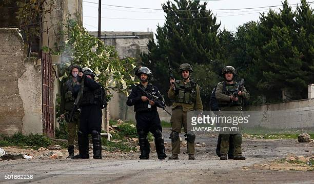 An Israeli borderguard fires a teargas canister at Palestinian protesters as fellow border guards and soldiers look on during clashes following a...