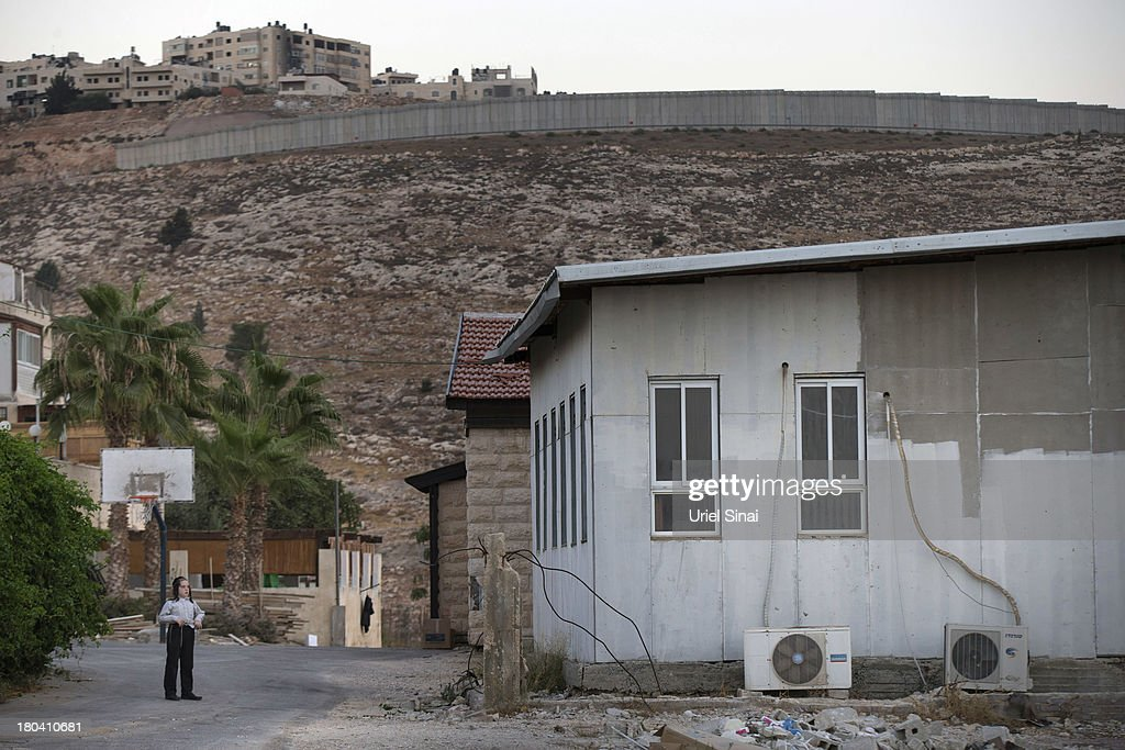 An Israeli boy looks on near the Israeli West Bank barrier in the Neve Yaakov neighborhood on September 12, 2013 in East Jerusalem, West Bank. The twenty-year anniversary of the Oslo Accord, which was to set up a framework for peace between Israel and Palestine, will be marked on September 13.