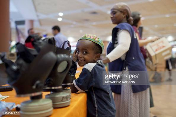An Israeli boy smiles near gasmasks at a distribution center in a shopping center in Mevaseret Zion on the outskirts of Jerusalem on July 25 2012...