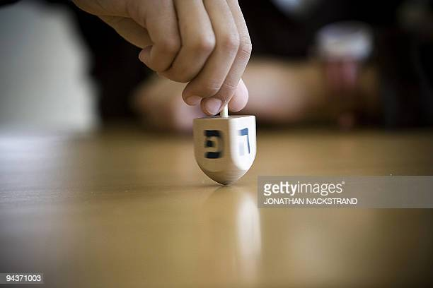 An Israeli boy spins a Dreidel as he takes part in a competition during the Jewish festival of Hanukkah in Tel Aviv on December 13 2009 A foursided...