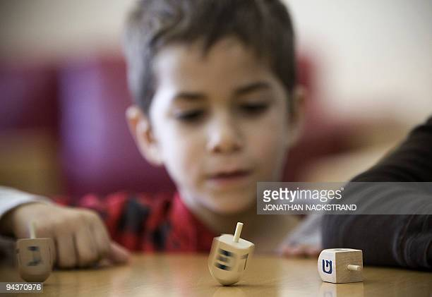 An Israeli boy takes part in a Dreidel competition during the Jewish festival of Hanukkah in Tel Aviv on December 13 2009 A foursided spinning top...