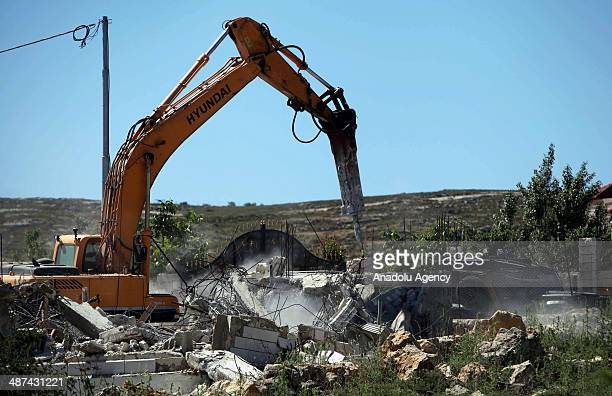 An Israeli bulldozer demolishes a house on April 30 2014 in AlAroub refugee camp near Hebron Israeli bulldozers backed by army troops on Wednesday...