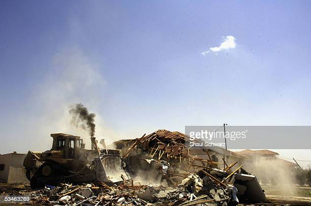 An Israeli bulldozer demolishes a house on August 25 2005 in the Jewish settlement of Gadid Gaza Strip The demolishing of the settlements in the...