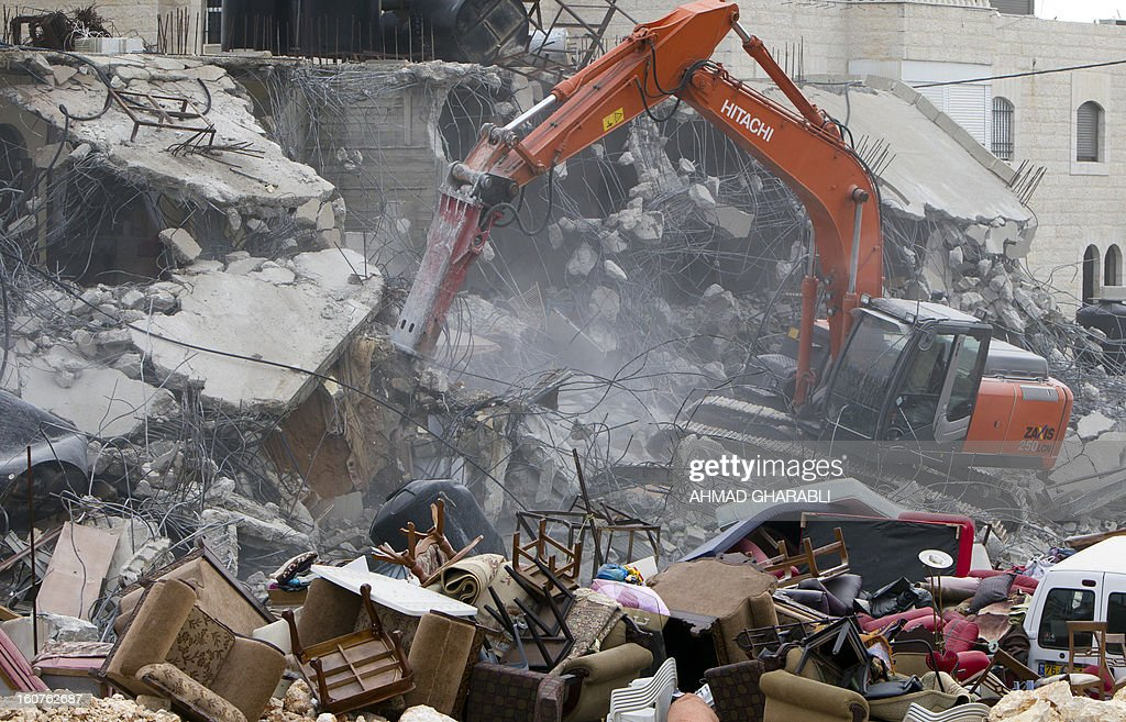 An Israeli bulldozer destroys a Palestinian house in the Arab east Jerusalem neighborhood of Beit Hanina on February 5, 2013. Palestinian homes built without a construction permit are often demolished by order of the Jerusalem municipality. AFP PHOTO/AHMAD GHARABLI