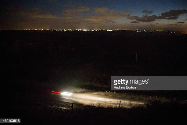 An Israeli car drives down the road with the Gaza strip's skyline in the background on the sixth day of Israel's operation 'Protective Edge' on July...