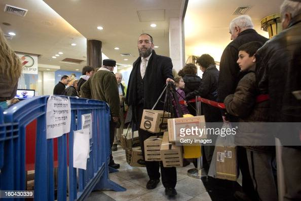 An Israeli carries gas mask kits collected from a distribution station in a mall January 31 in Pisgat Ze'ev East Jerusalem Israel Israel remains on...