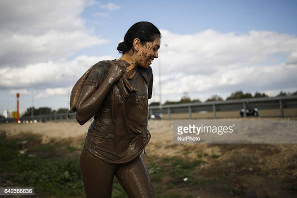 An Israeli carries heavy sandbags after crawling through mud during an annual combat fitness training competition in preparation for the compulsory...