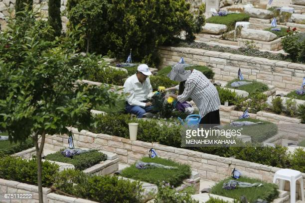 An Israeli couple visits the grave of their loved one at the Mount Herzel military cemetery in Jerusalem on April 30 a few hours ahead of the start...