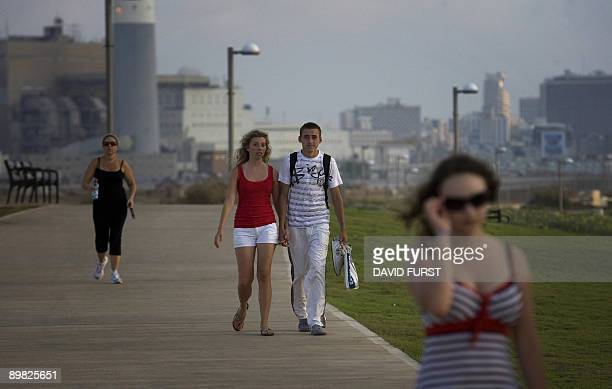 An Israeli couple walk along the boardwalk where an Israeli man was beaten to death late Friday evening by a gang of youths in the Tel Baruch...