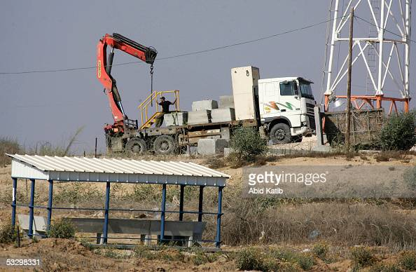 An Israeli crane removes cement blocks from an Israeli army post in the Israeli settlement of Doget on July 28 near the Palestinian town of Beit...