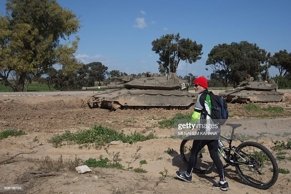 An Israeli cyclist walks with his bike past a Merkava tank guarded by an Israeli soldier, near the southern Israeli border with the Gaza Strip on February 6, 2016. / AFP / MENAHEM KAHANA