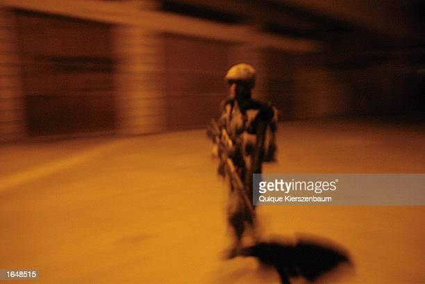 An Israeli Defense Forces paratrooper patrols the streets November 16 2002 in the West Bank town of Hebron The IDF seized all of the divided city in...