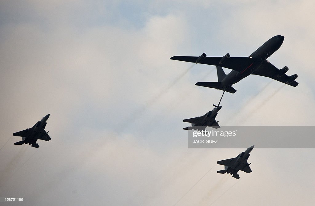 An Israeli F-15 fighter jet is refueled by a Boeing 707 during an air show at the graduation ceremony of Israeli pilots in the Hatzerim air force base in the Negev desert, near the southern Israeli city of Beersheva, on December 27, 2012. AFP PHOTO / JACK GUEZ