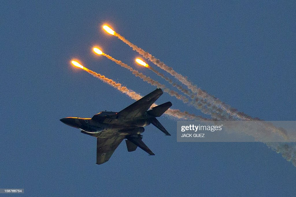 An Israeli F-15 I fighter jet launches anti-missile flares during an air show at the graduation ceremony of Israeli pilots at the Hatzerim air force base in the Negev desert, near the southern Israeli city of Beersheva, on December 27, 2012. AFP PHOTO / JACK GUEZ