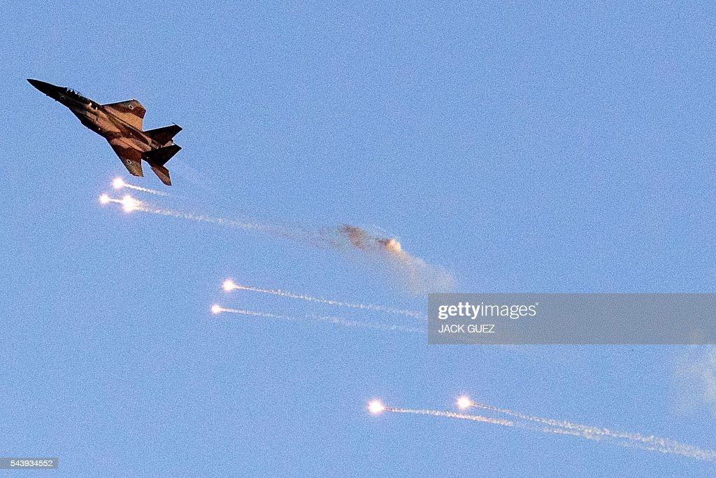 An Israeli F-15 I fighter jet launches anti-missile flares during an air show at the graduation ceremony of Israeli air force pilots at the Hatzerim base in the Negev desert, near the southern Israeli city of Beer Sheva, on June 30, 2016. / AFP / JACK