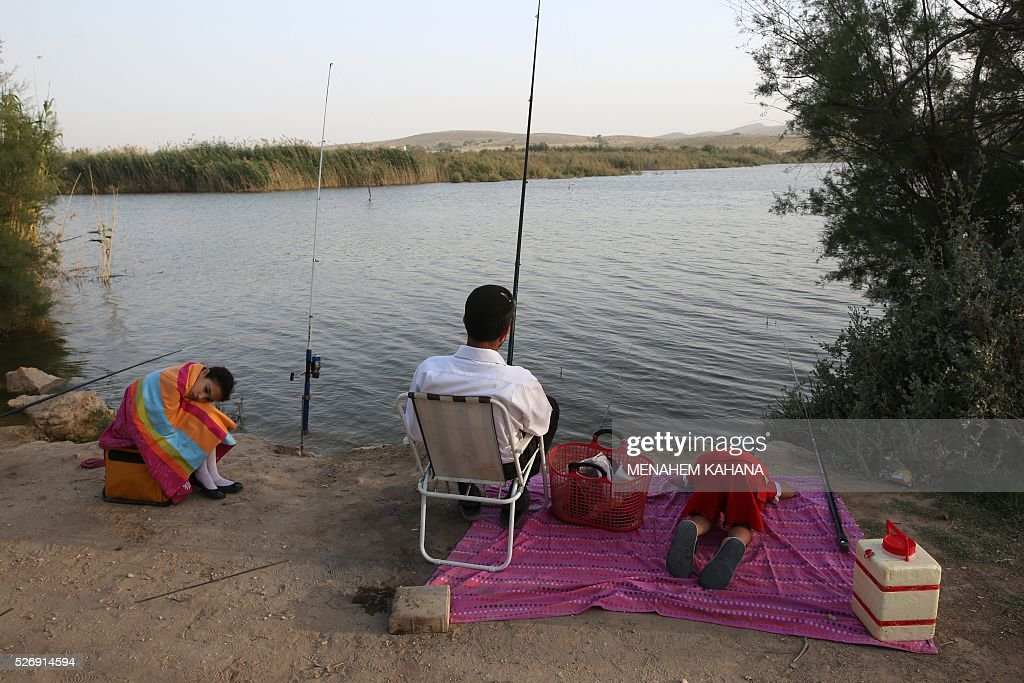 An Israeli family fish at the lake located next to the southern Israeli town of Yeroham in the Negev desert on May 1, 2016. / AFP / MENAHEM