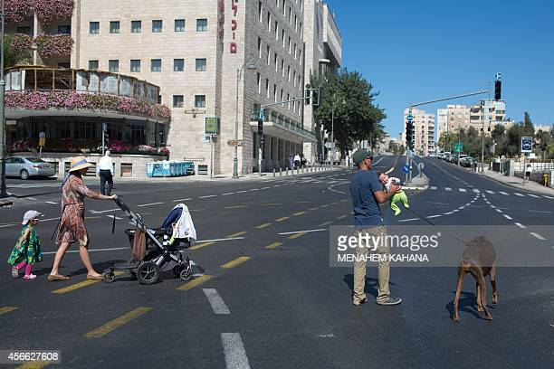 An Israeli family walks on a carfree road in Jerusalem during the solemn Jewish fast of Yom Kippur on October 4 2014 Yom Kippur which means the Day...