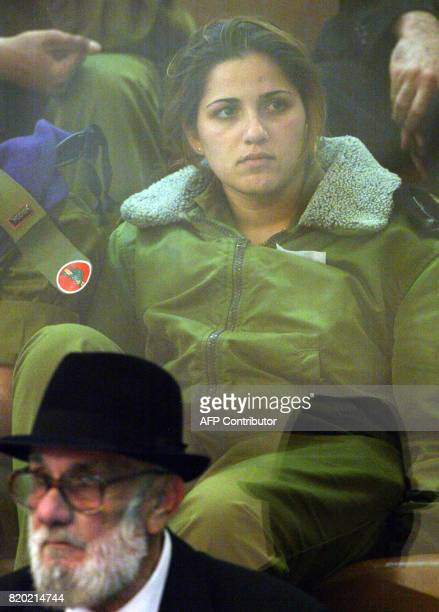 An Israeli female soldier and a civilian man sit behind protective glass as they watch and listen to Israeli Prime Minister Ariel Sharon give a...