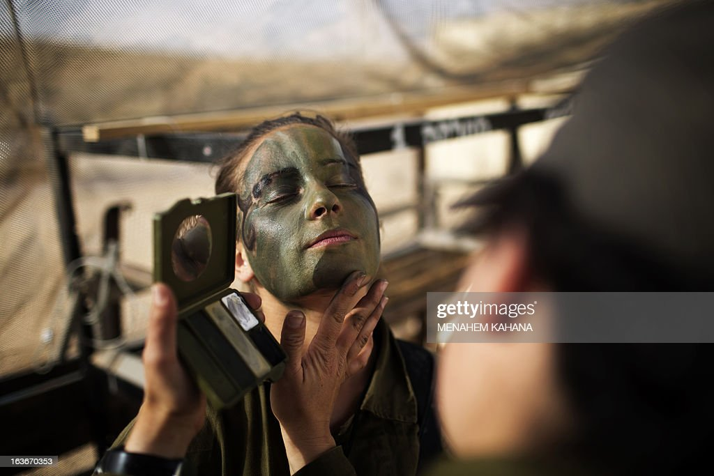 An Israeli female soldier of the 33rd Caracal Battalion has camouflage applied to her face prior to a graduation march in the northern part of the southern Israeli Negev desert, on March 13, 2013. The Caracal unit is an infantry combat battalion of the army, composed of both male and female soldiers mostly serving along the Israeli southern desert borders. AFP PHOTO/MENAHEM KAHANA