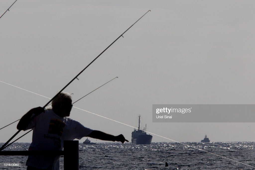 An Israeli fishermen is silhouetted in the foreground as the Rachel Corrie aid ship (C) enters the military port of Ashdod in southern Israel after it was intercepted by the Israeli Navy on June 5, 2010, in Ashdod, Israel. Israel, which has faced international criticism over the deadly May 31 raid on a ship carrying humanitarian aid to the Gaza Strip, seized the Rachel Corrie today preventing it from reaching Gaza.
