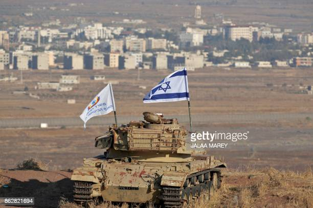 An Israeli flag flutters above the wreckage of an Israeli tank sitting on a hill in the Israelioccupied sector of the Golan Heights and overlooking...