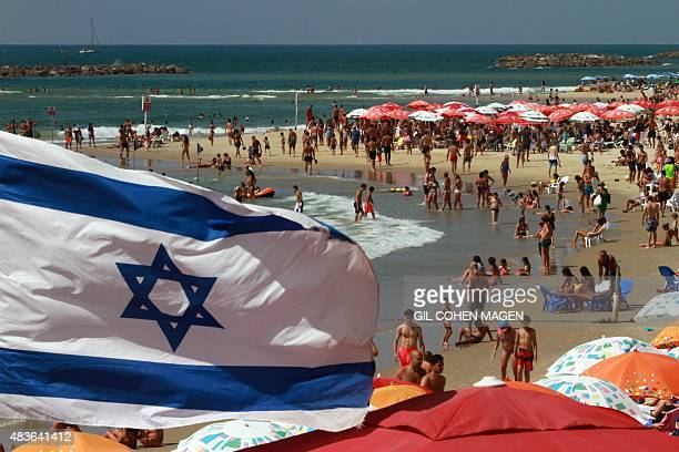 An Israeli flag flutters above umbrellas on the beach in the Mediterranean city of Tel Aviv on August 11 2015 Decision to dedicate a day of beach...