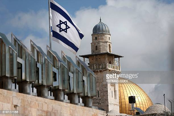 An Israeli flag is seen fleeting in front of a minaret and the Dome of the Rock on the AlAqsa mosque compound in Jerusalem's Old City on March 17...