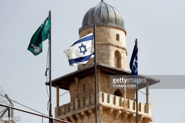 An Israeli flag waves in front of one of the minarets of the Aqsa mosque compound just outside the Western Wall in the Old City of Jerusalem on April...