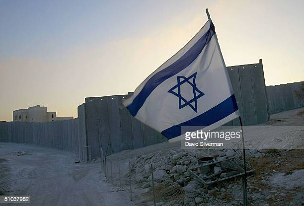 An Israeli flag welcomes the dawn over Israel's separation barrier July 9 2004 where the 9meterhigh concrete wall cuts the West Bank Palestinian...