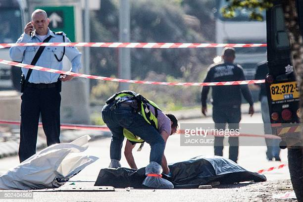 An Israeli forensic policeman stands next to the body of a Palestinian assailant who was shot dead after he stabbed two Israeli security guards at an...